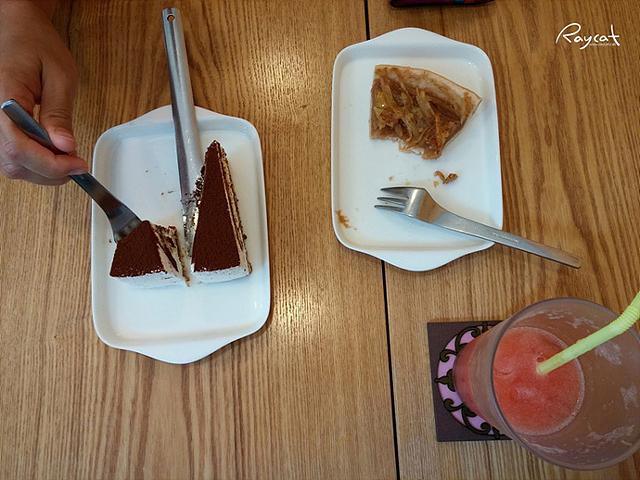 초콜릿 조각 케이크를 흰색 접시에 담아 먹고있는 모습. 아래 쪽으로는 음료수도 보인다.
