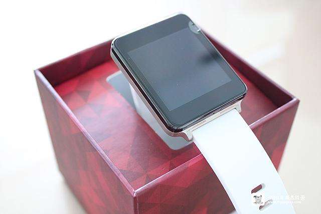 LG G워치 화이트 컬러가 붉은색 박스에 놓여져 있다