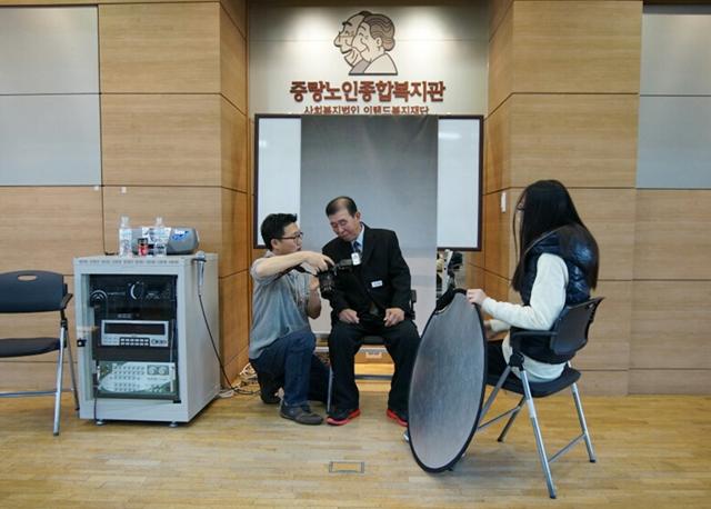 중랑노인종합복지관 앞에서 어르신의 증명사진을 찍어주고 있는 모습