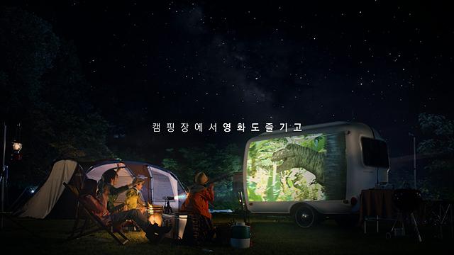 캠핑장에서 즐기는 미니빔. 어두운 캠핑장에서 미니빔 TV로 영화를 보는 모습