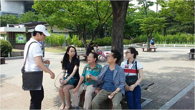 홀몸어르신들의 나들이를 함께하는 행복가꿈이 팀. 나무 밑에 앉아있는 어르신과 대화를 나누고 있다.