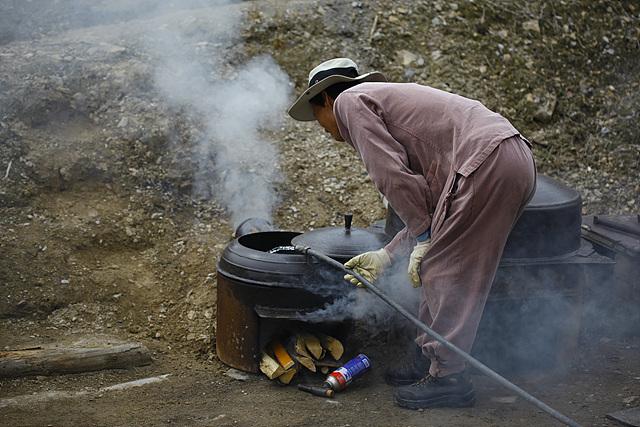 한 남성이 솥에 물을 넣고 있다. 솥에는 연기가 나고 있다.