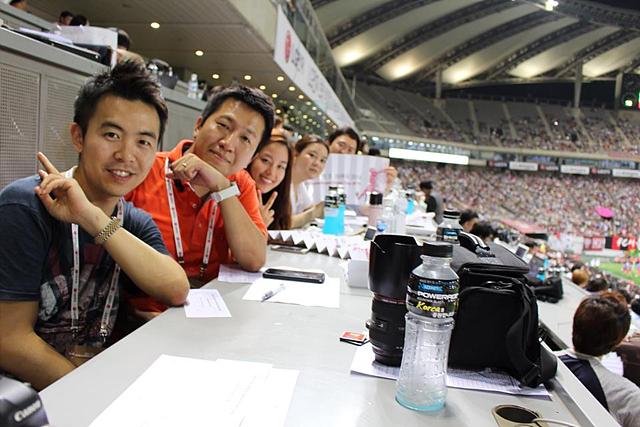 기자석에 앉아서 경기를 관람하고 있는 더 블로거의 모습. 카메라와 음료수 병이 보인다.