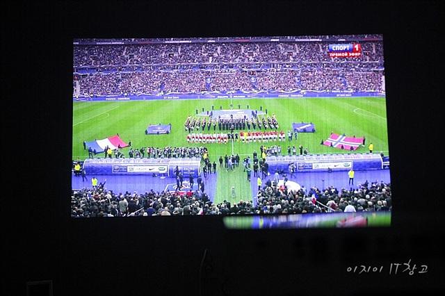 미니빔TV로 송출하는 스크린에 축구 경기가 방영되고 있다.