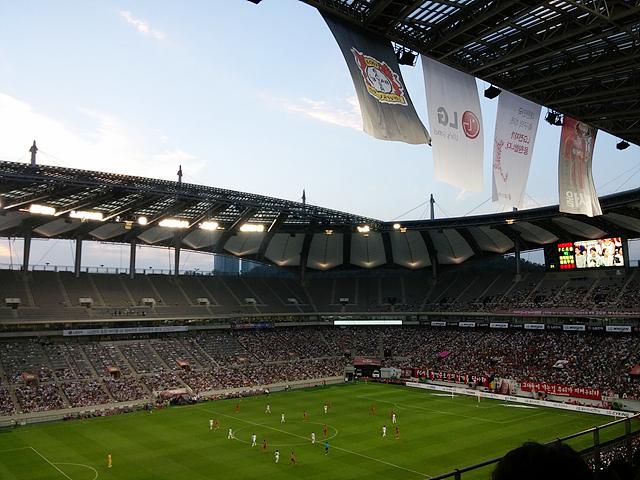 레버쿠젠 경기가 열리는 상암 월드컵 경기장. 펄럭거리는 깃발 아래로 선수들과 관중들, 축구경기장이 보인다.