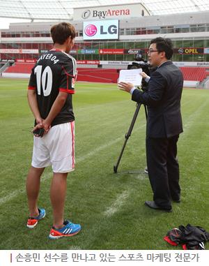 손흥민 선수가 축구장에서 스포츠 마케팅 전문가의 인터뷰에 응하고있다.