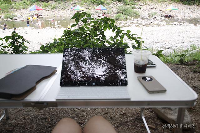 캠핑 테이블 위에 놓인 LG전자 탭북. 뒤로는 계곡이 보인다.
