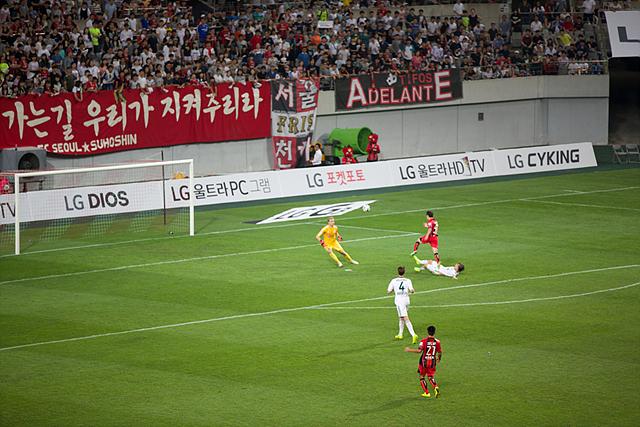 격렬하게 경기 중인 선수들. 레버쿠젠 골키퍼가 공을 막기 위에 움직이고 있다.