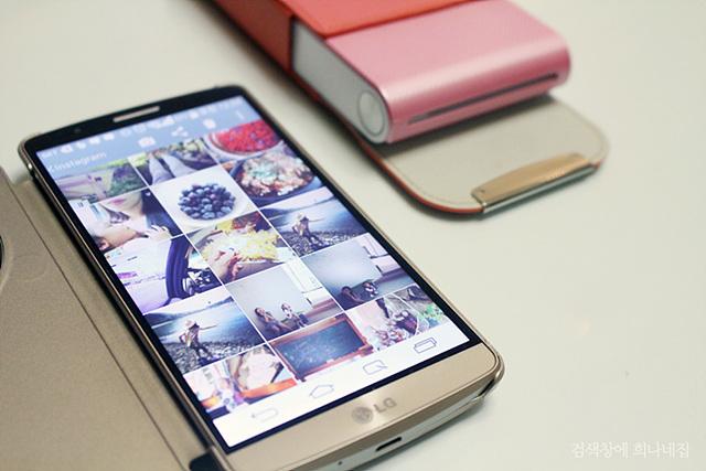 켜진 스마트폰에 여러 장의 사진이 보인다. 뒤로는 LG 포켓포토가 보인다.