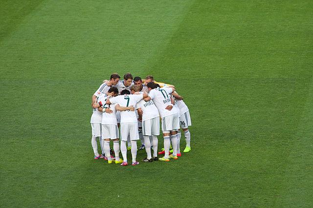 둥글게 모여서 화이팅을 다짐하는 레버쿠젠 선수들. 흰색 유니폼을 입고 있다.