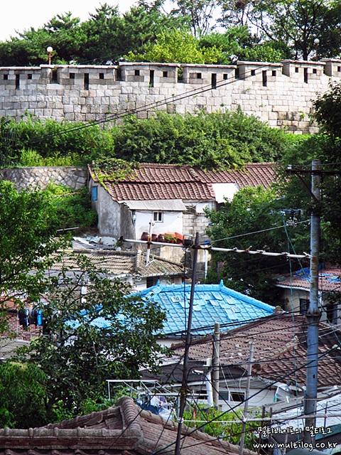 기와 지붕들 사이에 하늘색 기와 지붕이 눈에 띈다. 뒤로는 성북동 성곽길이 보인다.