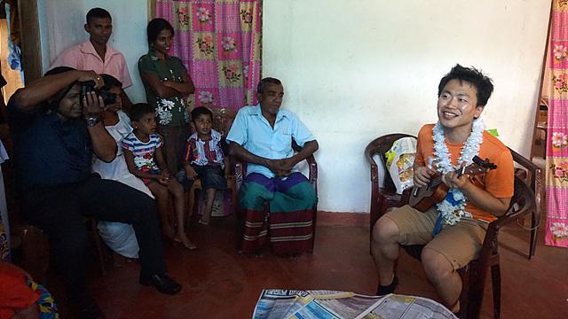 우쿨렐레를 들고 노래를 부르는 조대득 연구원과 웃으며 경청하는 스리랑카 사람들
