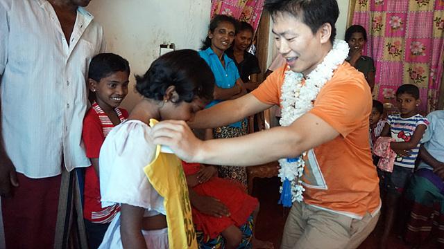 스리랑카 소녀에게 선물인 티셔츠를 건네는 모습