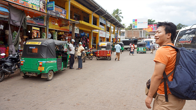 비빌리로 배낭을 매고 이동하는 모습. 작은 자동차와 길거리 상점이 보인다.