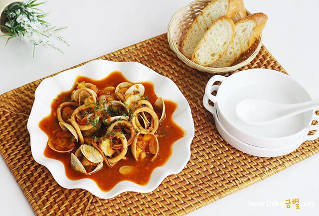 전복 해산물 수프가 그릇에 담겨 있다. 옆에는 함께 먹을 바게트가 놓여 있다.