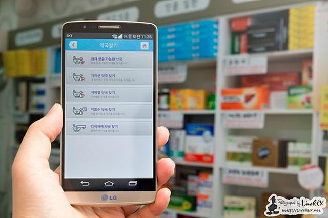 약국을 배경으로 약국찾기 어플리케이션 페이지가 구동되는 스마트폰을 한 손으로 들고 있다.