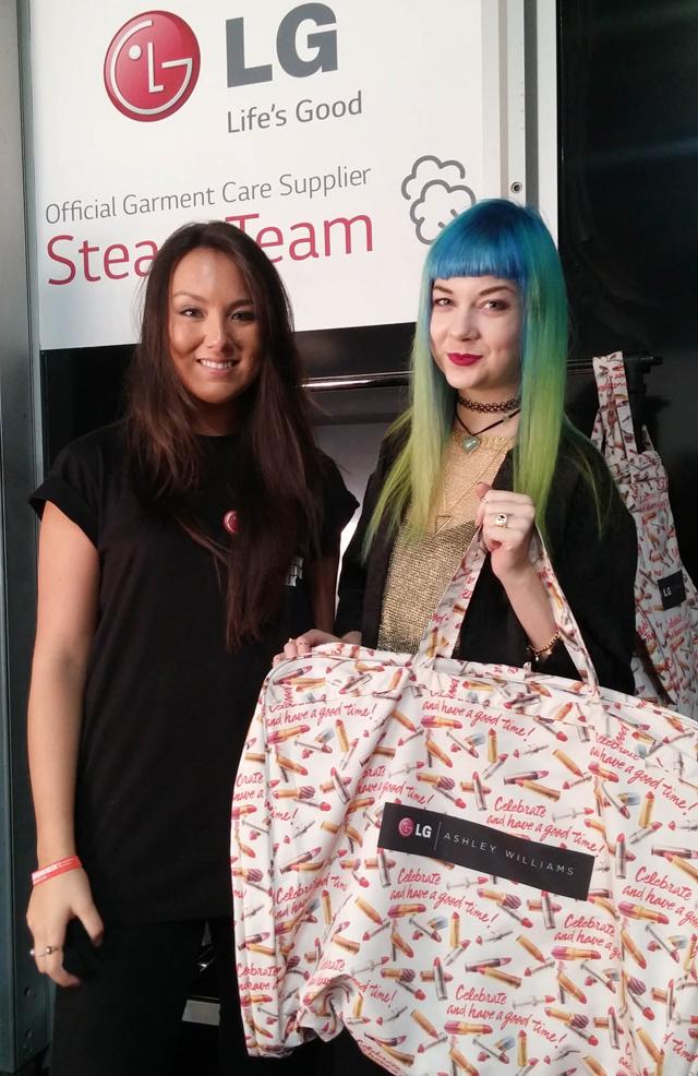LG전자 '스팀팀(Steam team)' 직원과 행사장을 찾은 참가자가 LG전자와 패션 디자이너 애쉴리 윌리암스(Ashley Williams)가 협업해 만든 의류 가방을 들고 포즈를 취하고 있습니다.