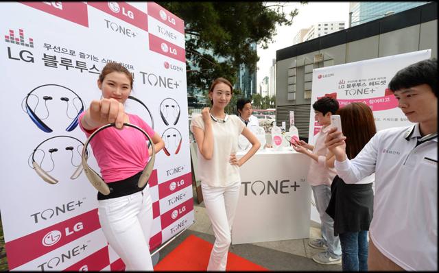 모델이 서울 강남역 행사장에서 'LG 톤플러스'를 손에 들고 포즈를 취하고 있습니다.