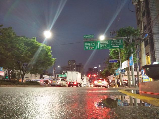 비온 뒤 갠 서울의 거리. 아스팔트 위 빗물이 고여있다.