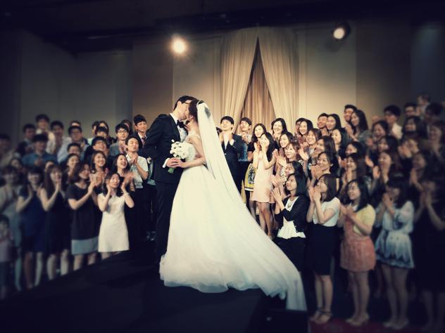 결혼식 장면. 신랑 신부가 입을 맞추고 하객들이 박수를 치고 있다.