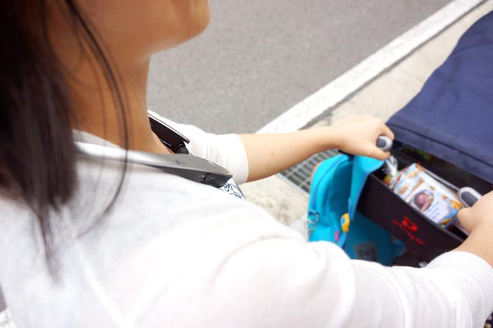 LG 톤플러스 HBS-900를 착용하고 두 손으로 유모차를 밀고 있다.