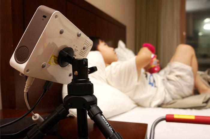 침대에 누워있는 아이를 배경으로 LG 미니빔TV가 보인다.