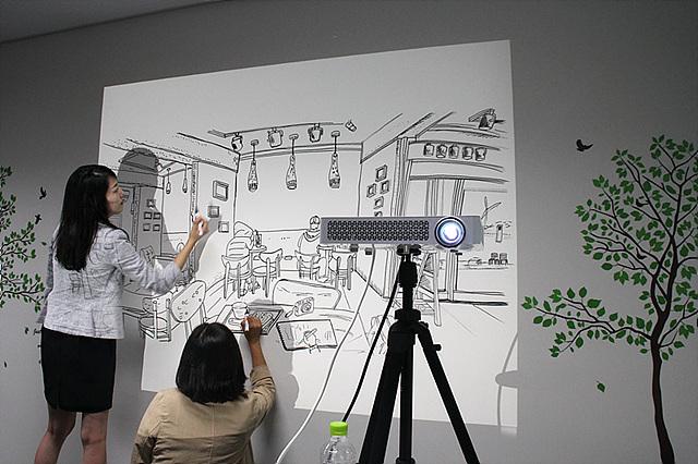 LG 미니빔을 통해 직원들이 벽화를 그리고 있다.