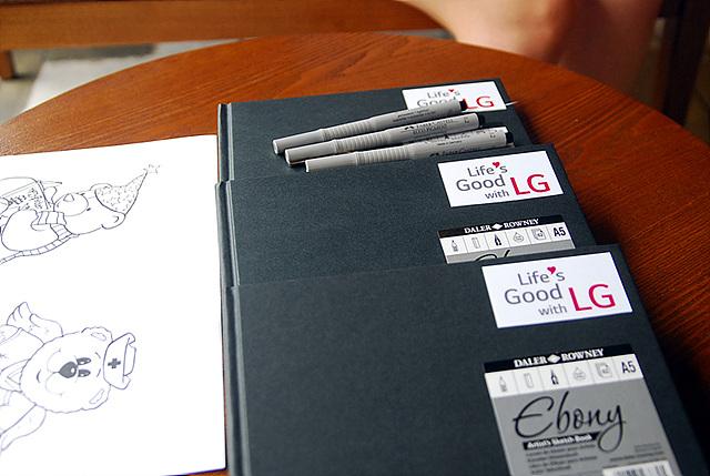노트와 펜이 책상 위에 올려져 있다. 노트에는 'Life's Good LG'문구가 보인다.