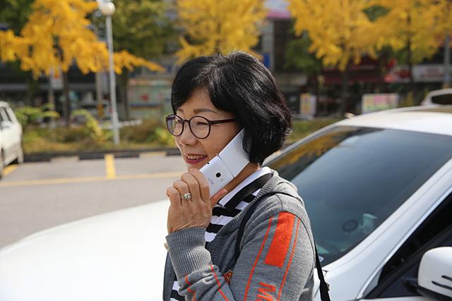 중년의 여성이 와인스마트폰으로 전화를 받고 있다.