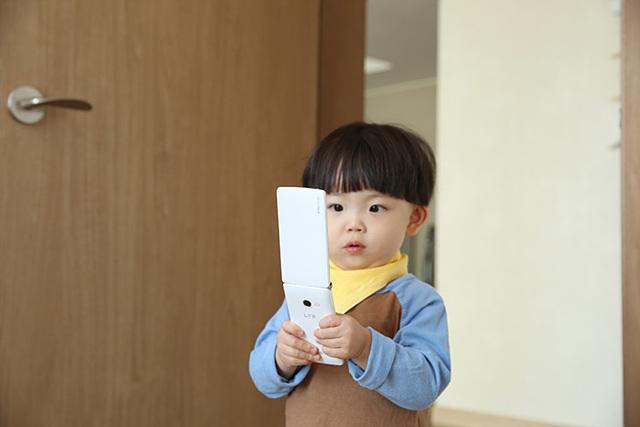 어린아이가 와인스마트폰을 들고 있다.