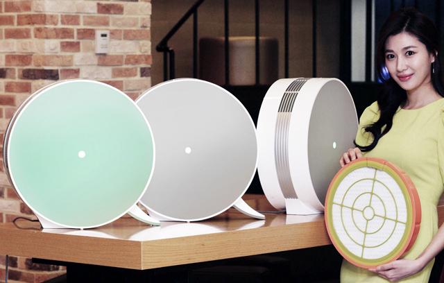 모델이 원형 디자인의 '몽블랑' 공기청정기 신제품을 소개하고 있는 모습 입니다.