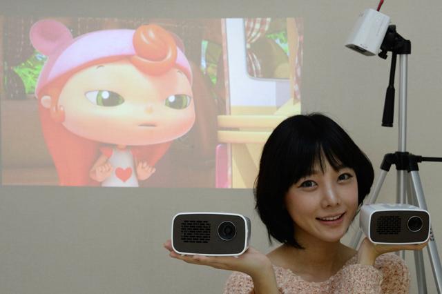 모델이 '초경량 미니빔TV'로 영상을 즐기고 있는 모습 입니다.