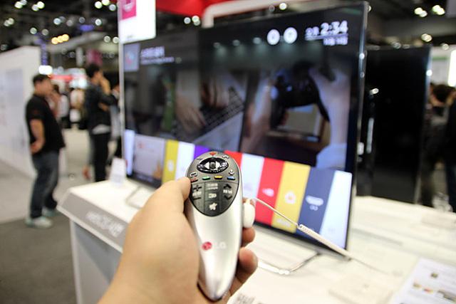 LG 스마트+ TV의 리모콘을 조작하고 있다.