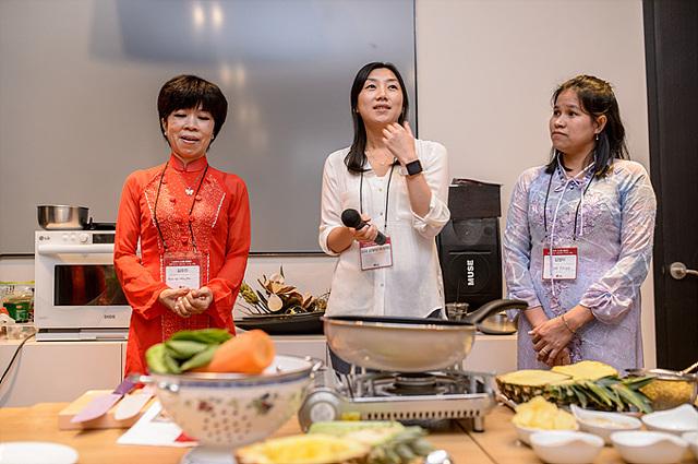 블로거 금별맘님이 파인애플 볶음밥을 만드는 방법에 대해 설명하고 있다. 양 옆에는 베트남 주부가 서있다.