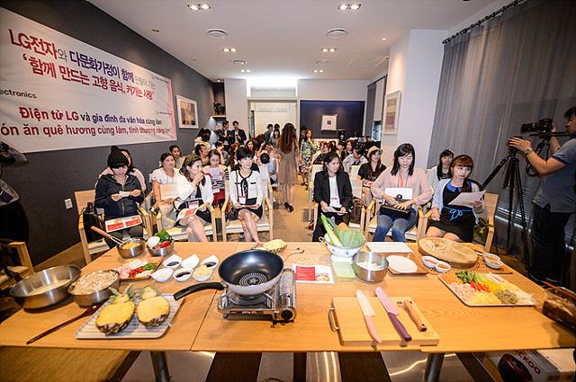 베트남출신 주부 및 한국인 주부 약 100명이 앉아서 쿠킹클래스를 기다리고 있다. 탁상 위에는 음식 도구와 재료가 보인다.