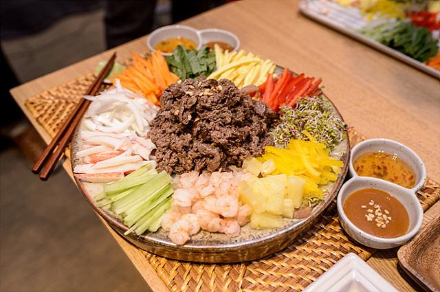 완성된 한국식 월남쌈. 다양한 야채가 다듬어져 그릇에 담겨 있다. 옆에는 소스도 보인다.