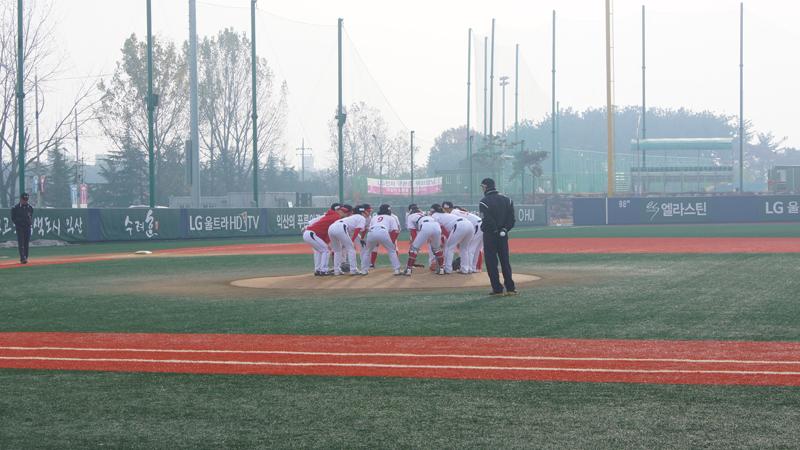 선수들이 경기 시작 전 그라운드 중앙에서 모여 화이팅을 외치고 있다.