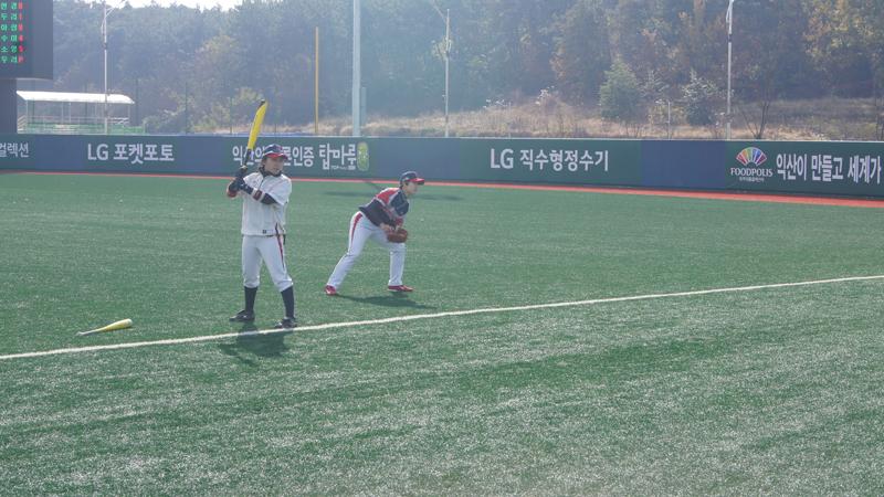 서울 비밀리에와 구리 나인빅스의 경기 시작 전 몸을 푸는 선수들의 모습. 한 선수는 야구배트를 들고 서있고 뒤에 한 선수는 글러브를 낀채 상체를 숙이고 있다.