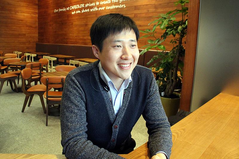 한국영업본부 위용석 대리가 테이블에 앉아 미소를 짓고 있다.