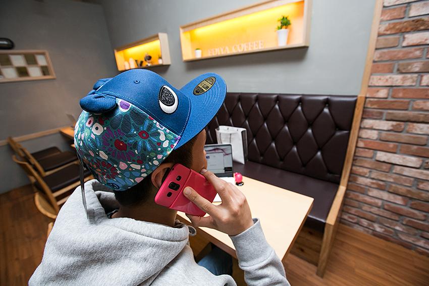 파란색의 아카 스냅백을 쓰고 아카 스마트폰으로 통화하고 있는 모습