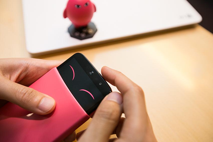 버튼을 누르자 웃는 표정이 나타나는 핑크색 아카폰