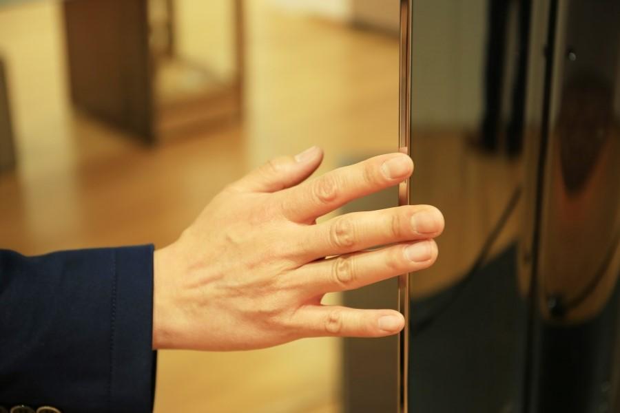 LG전자 울트라 올레드 TV의 두께감을 확인하기 위해 손을 대고 있다.