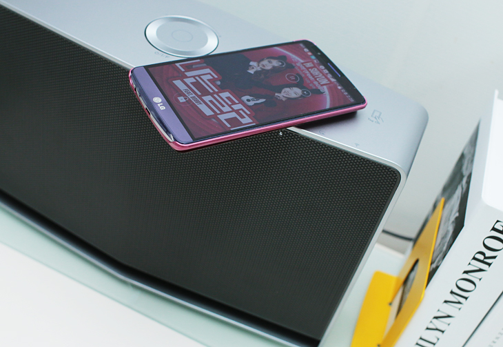 스마트 오디오 태그 기능을 통해 스마트폰으로 음악을 재생하고 있다. LG 스마트 오디오 위에 스마트폰이 놓여 있다.
