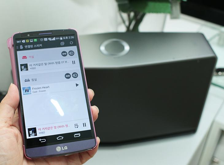 스마트폰 창에 거실과 침실에 있는 두 개의 스마트 오디오가 연결되었다는 표시가 나온다. 스마트폰 뒤에 LG 스마트 오디오가 보인다.
