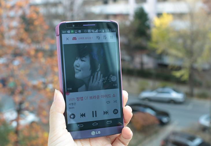 블루투스를 통해 스마트폰으로 음악을 재생하고 있다. 스마트폰 뒤에는 주차장이 보인다.