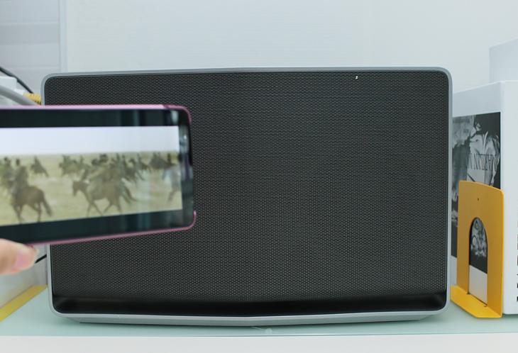 블루투스를 통해 스마트폰으로 음악을 재생하고 있다. 스마트폰 뒤에는 탁상 위에 놓여 있는 LG 스마트 오디오가 보인다.