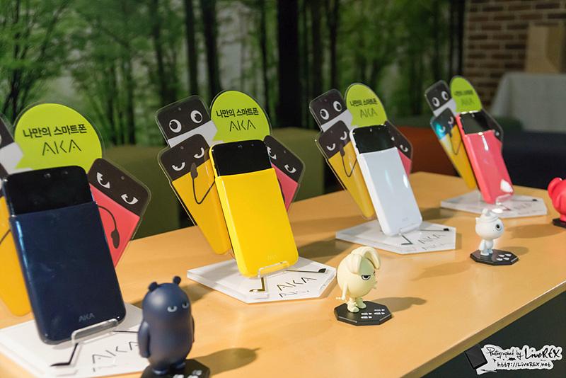LG 아카 스마트폰이 '소울(Soul, 네이비)', '에기(Eggy, 옐로)', '우키(Wooky, 화이트)', '요요(YoYo, 핑크) 순으로 전시되어 있다. 각 아카 스마트폰 앞에는 아트토이가 놓여 있다.