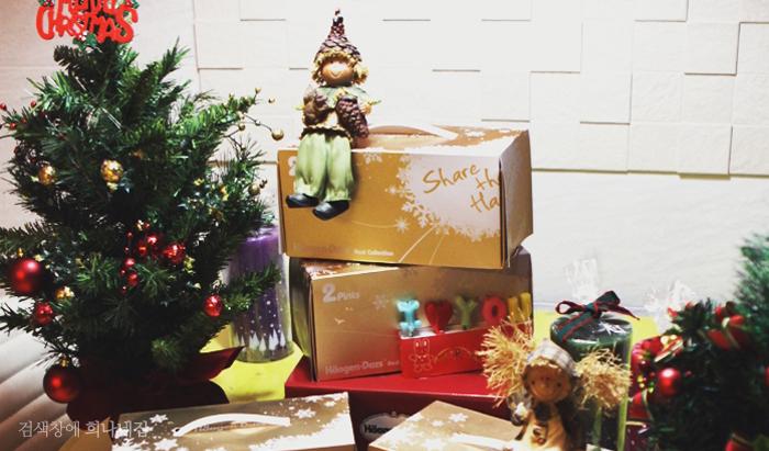 크리스마스 트리와 쌓여있는 선물 상자 위로 인형이 놓여져 있다.