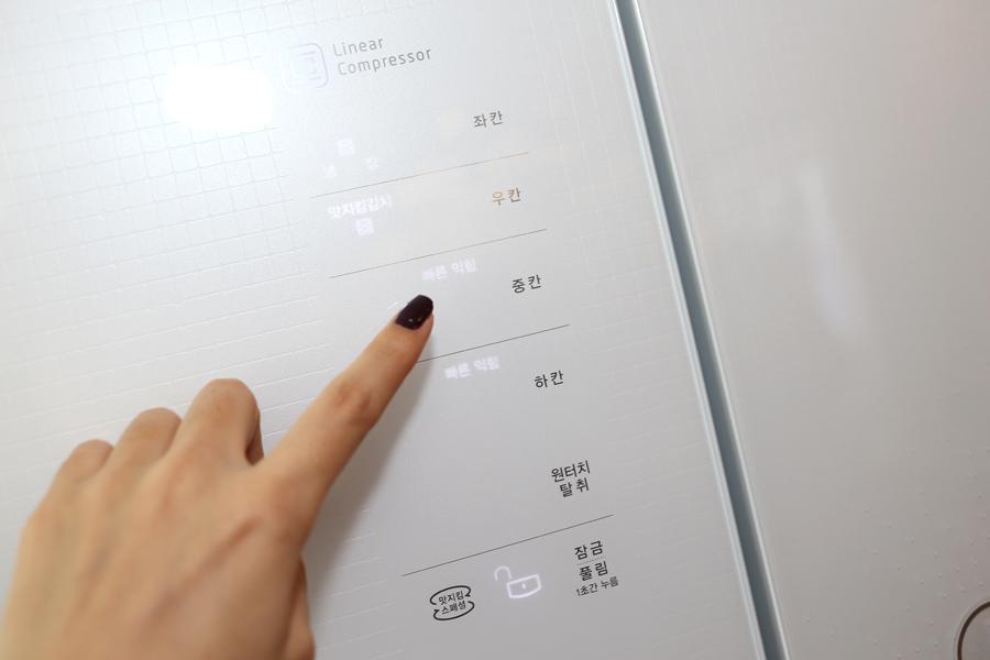 LG 디오스 김치톡톡 냉장고 전면부를 손으로 터치하고 있다.