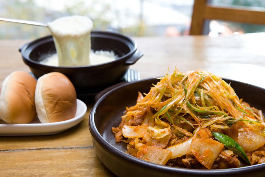 돼지고기 김치 퐁듀. 김치, 파와 함께 볶은 돼지고기와 치즈, 빵이 보인다.